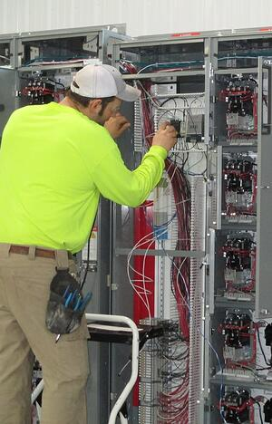 A control system provider connecting wires at a panel